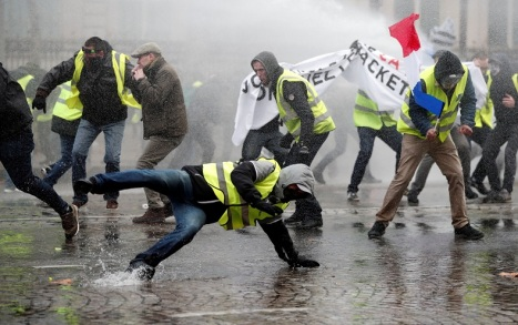 Protesters wearing yellow vests, a symbol of a French drivers' protest against higher fuel prices, face a water canon fired by police during clashes on the Champs-Elysees in Paris