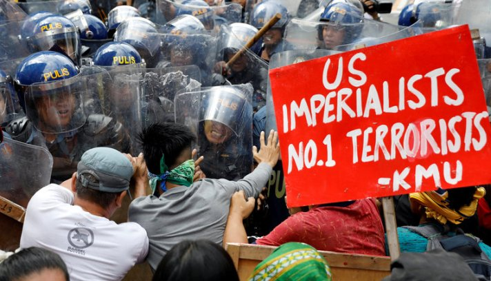 Protesters clash with anti-riot police officers as they try to march towards the U.S. embassy during a rally against U.S. President Donald Trump's visit, in Manila